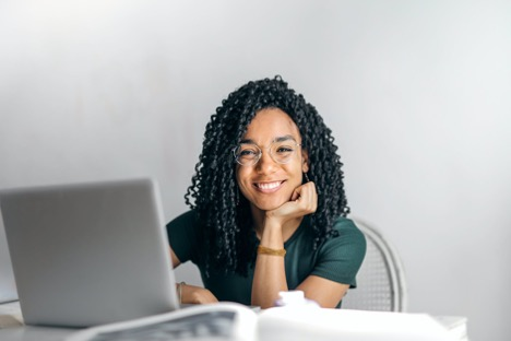Black woman with glasses smiles with a laptop on her desk